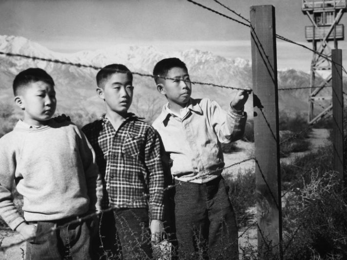 "Toyo Miyatake, ""Boys Behind Barbed Wire (Norito Takamoto, Albert Masaichi, and Hisashi Sansui),"" 1944 [detail]. Gelatin silver print. Courtesy of Alan Miyatake, Toyo Miyatake Manzanar Collection."