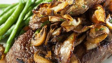 Prime ribeye topped with mushrooms and onions at 555 East American Steakhouse